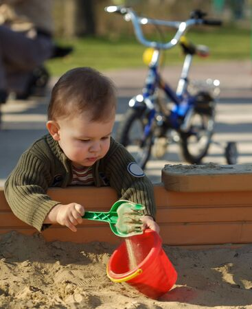 sand pit: Young boy is playing outdoor in a sand pit.