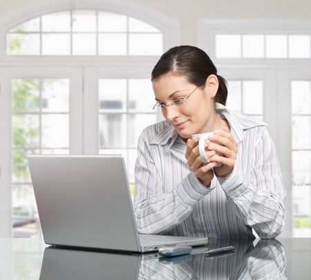 sinecure: Young woman looks at her laptop computer and drinks her coffe. It is early morning in a light and clean home interior dominated by white and soft tones.