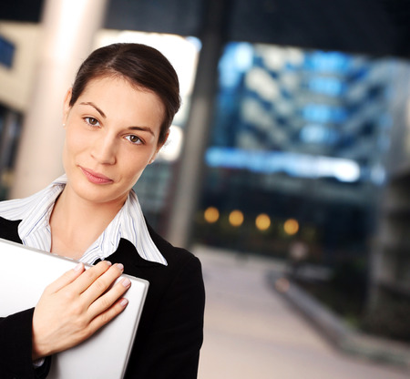 Young businesswomen is posing with laptop in front of an officebuilding. Stock Photo