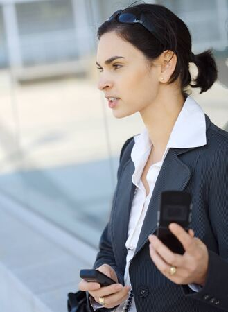 Young businesswoman is using two mobile phones at the some time. She is outdoor, somewhere in the downtow district. Stock Photo - 1414067