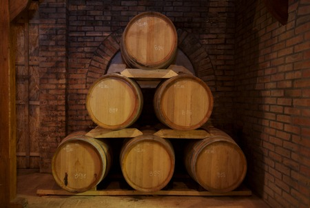cellars: Wine barrels stacked in the old cellar of the winery. Stock Photo