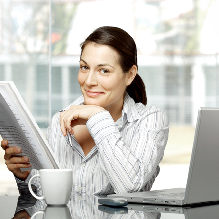 good looking woman: Young businesswoman is reading a paper document in front of the office window. She also has a laptop on her desk. Stock Photo
