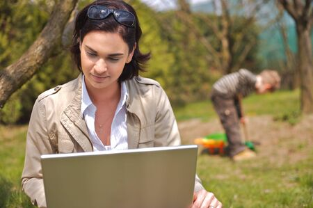 sinecure: Attractive young mother is sitting on the ground in the garden and using a laptop while a 5 years old boy is playing in the background. Stock Photo