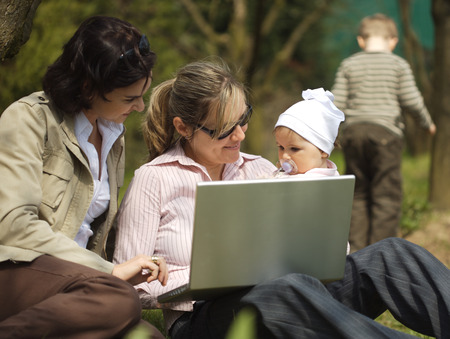 sinecure: Young mothers are sitting on the ground in the garden and using a laptop.