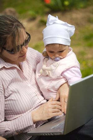 sinecure: Mother of a 9 months old baby-girl is sitting on the ground in the garden and uses a laptop computer.