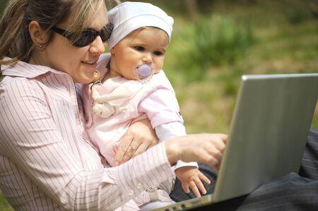 outwork: La madre de una vieja bebe-muchacha de 9 meses se est� sentando en la tierra en el jard�n y utiliza una computadora de computadora port�til.