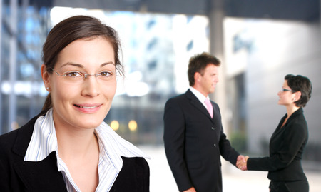 forground: Young businesswoman is smiling in the forground while other businesspeople are shaking hand in the background.