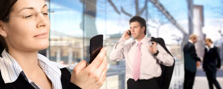 Businesspeople are calling on mobiles in front of a modern office building. photo
