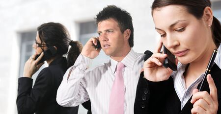 Businesspeople are calling on mobiles in front of an office building. Stock Photo - 1414080
