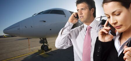 Very busy young businesspeople talk on mobiles. They are on the runaway in front of a corporate jet. photo