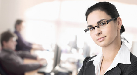 Businesspeople work in the office while a businesswomen stands in the foreground. Stock Photo - 1422815