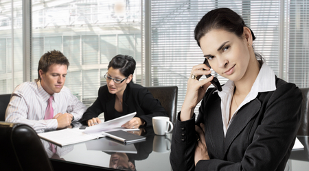 Businesspeople work in the office while a businesswomen talks on mobile in the foreground.