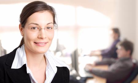 especialistas: Administrador de mujeres j�venes est� en la oficina con especialistas en TI est�n trabajando en un segundo plano.