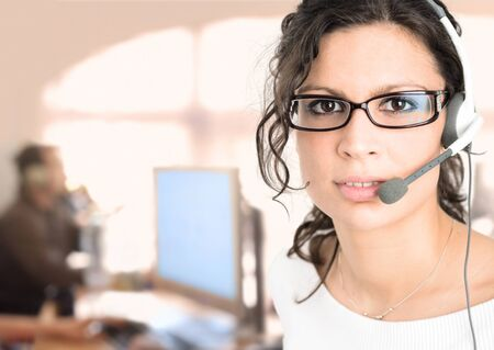Young female customer service representative recieves calls on a headset while an IT specialist works on a computer in the background. Stock Photo - 1422660