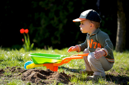 citypark: 2 years old boy plays with toy tools in the garden. Stock Photo