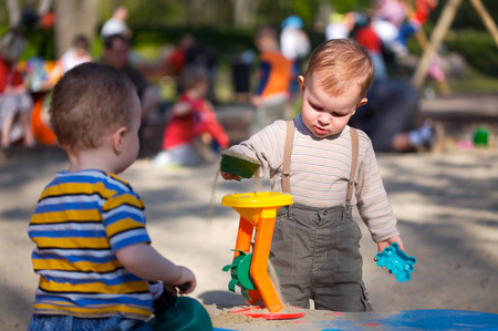 2 years old children are playing together in the sandbox Stock Photo