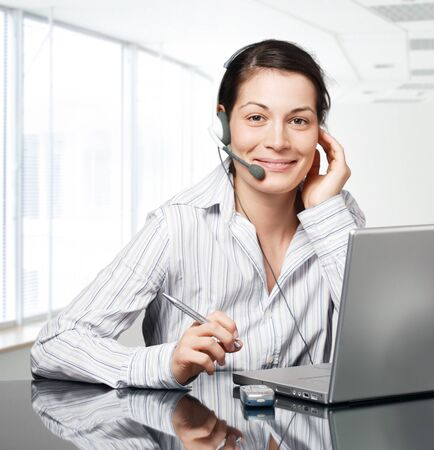 telework: Young and smiling operator works on a laptom computer in a modern office.