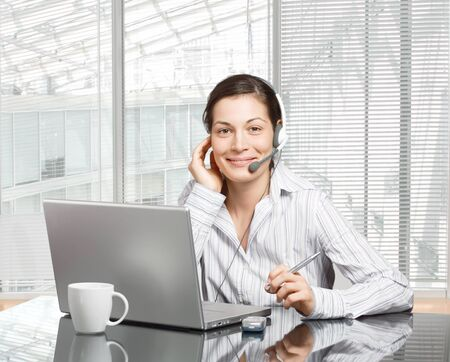 Young and smiling operator works on a laptop computer in a modern office. Stock Photo - 1414252