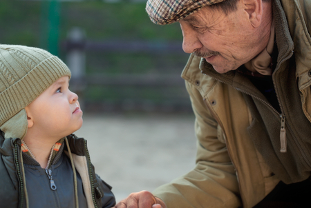 Grandfather and his 2 years old grandson looking at each other.  Stock Photo - 1422596