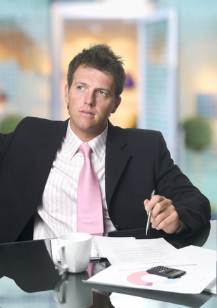 Handsome businessman sits behind his office desk. Stock Photo - 1414151