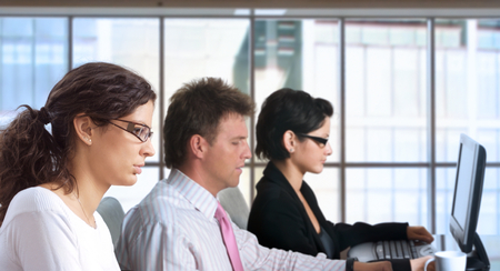 Young office workers are sitting in front of their computer screens. Stock Photo - 1422473