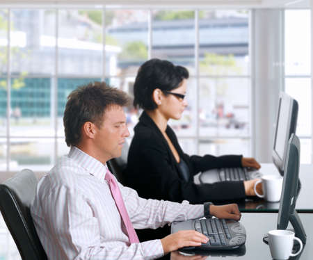 Young office workers are sitting in front of their computer screens. Daylight, indoor, office. Stock Photo - 1422477