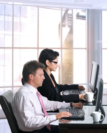 Young office workers are sitting in front of their computer screens. Daylight, indoor, office. Stock Photo - 1422865