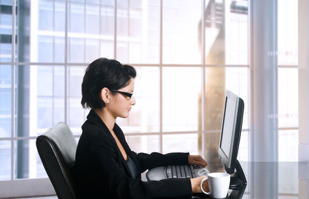 Young female office worker sits in front of her computer screen. Daylight, indoor, office. Stock Photo - 1414199