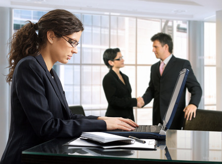 Young female secretary makes notes on a laptop  while other business people are shaking hands in the background. Daylight, indoor, office. Stock Photo - 1414240