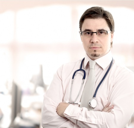 Male doctor in front of his office window. Daylight, indoor.