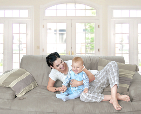 home comfort: Mother and baby laugh together at home. They are sitting on the sofe in a brightly lit living room.