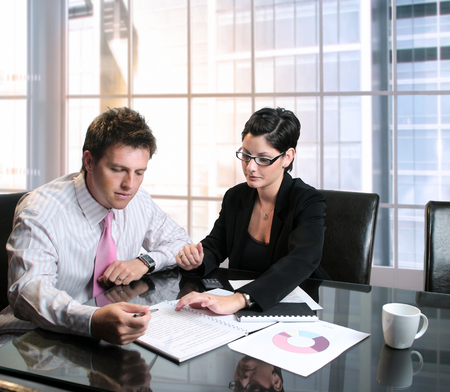 Young businesspeople work with documents and charts in the meeting room. photo