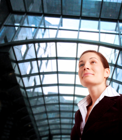 Young and ambitious businesswoman looks at the future in front of an office building. Stock Photo