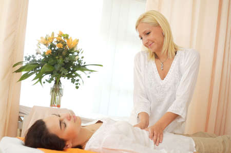 womanliness: Beautician massages a patient in the beauty salon. Stock Photo