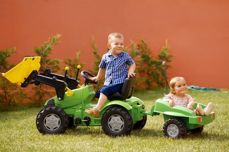 two years: One year old  girl and two years old boy are playing together outdoor in the garden. Stock Photo