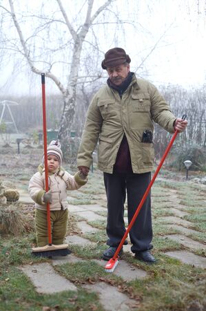 Grandpa and grandson spend time together outdoor in the garden on a cold winter day. photo