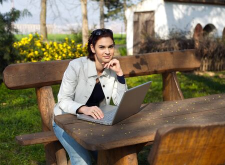 sinecure: Young woman works on a laptop computer outdoor.