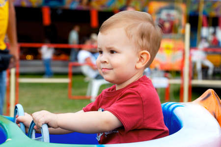 Two years old child driving toy vehicle in the amusement park. photo