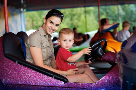 theme park: Mother and 2 years old  pay drive dodgem together in the theme-park.