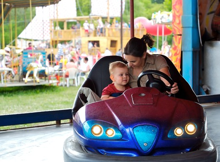 2 years old: Mother and 2 years old  pay drive dodgem together in the theme-park.