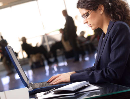Businesswoman works on laptop in the lobby. Stock Photo - 1414195