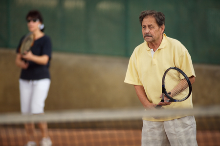 Active senior man in his 70s plays tennis. photo