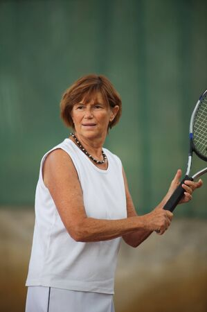 Active senior woman in her 60s plays tennis. photo