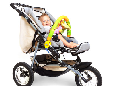 One year old  boy is sitting in a stroller, smiling and playing with toys. All toys visible on the photo are officialy property released. Stock Photo - 1414172