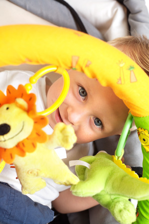 One year old  boy is sitting in a stroller, smiling and playing with toys. All toys visible on the photo are officialy property released. Stock Photo - 1422600