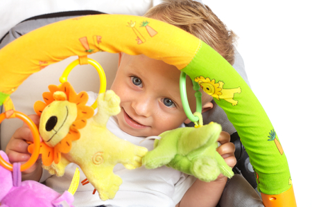 One year old baby boy is sitting in a stroller, smiling and playing with toys. All toys visible on the photo are officialy property released.  Stock Photo - 1414310