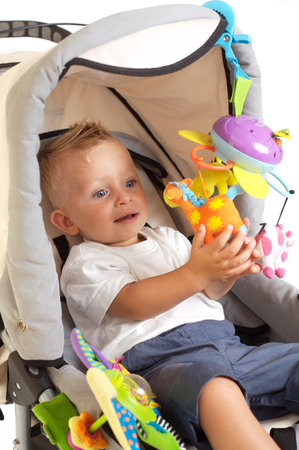 One year old  boy is sitting in a stroller, smiling and playing with toys. All toys visible on the photo are officialy property released. Stock Photo - 1422635