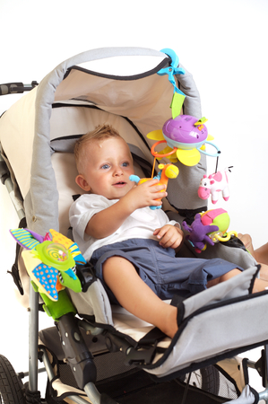 One year old  boy is sitting in a stroller, smiling and playing with toys. All toys visible on the photo are officialy property released.  Stock Photo - 1422500