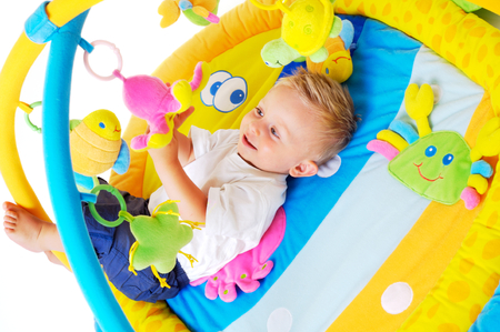 One year old baby boy enjoys playing with toys. Studio Shot. All toys visible on the photo are officialy property released. Stock Photo - 1422740