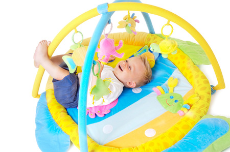 One year old  boy enjoys playing with toys. Studio Shot. All toys visible on the photo are officialy property released. Stock Photo - 1414208